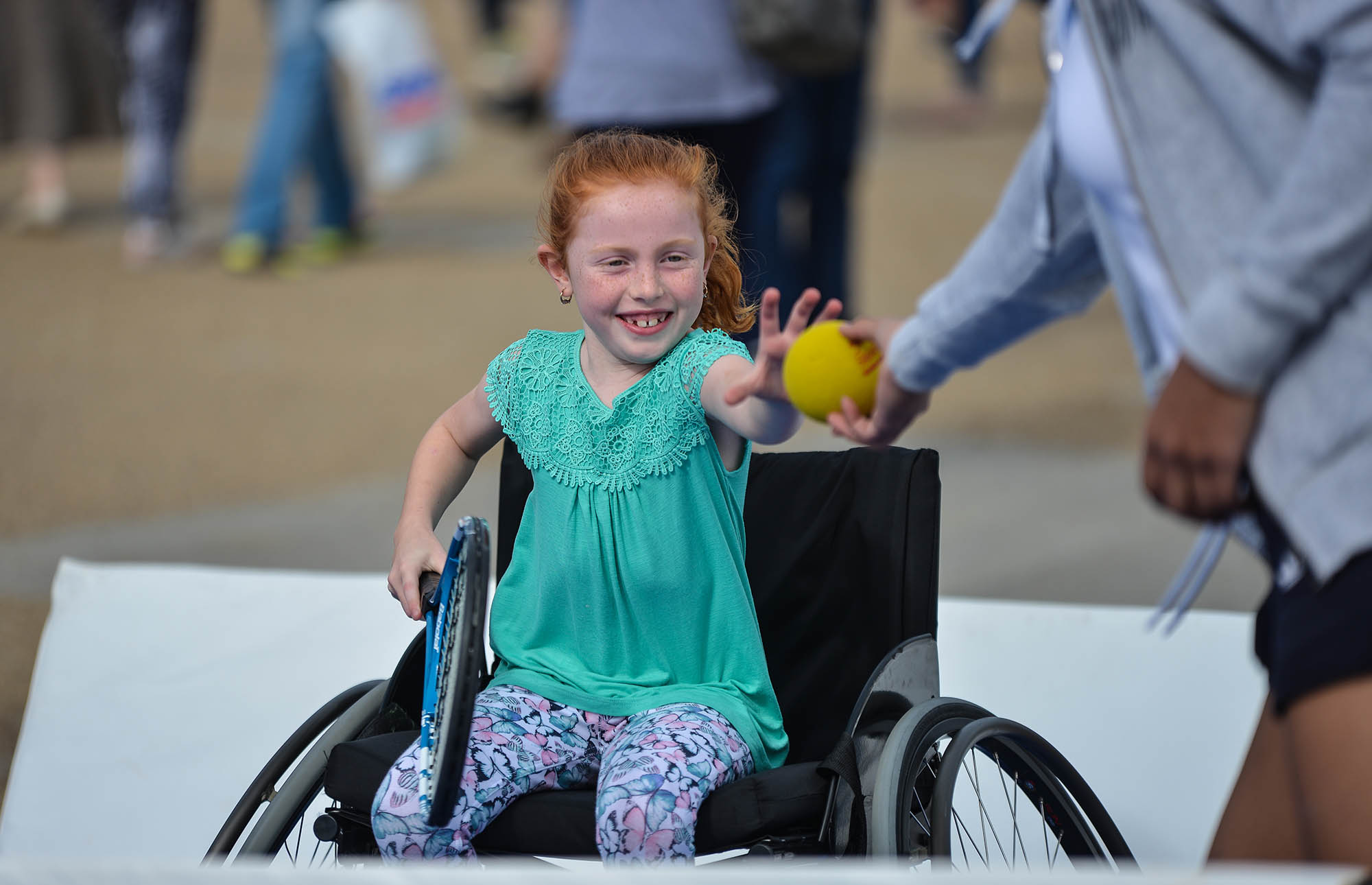 girl in wheelchair grabbing ball