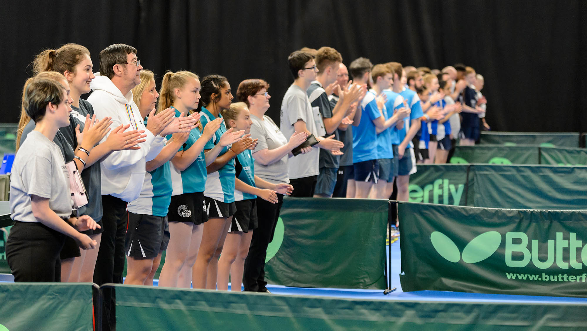 group of people applauding indoor table tennis action