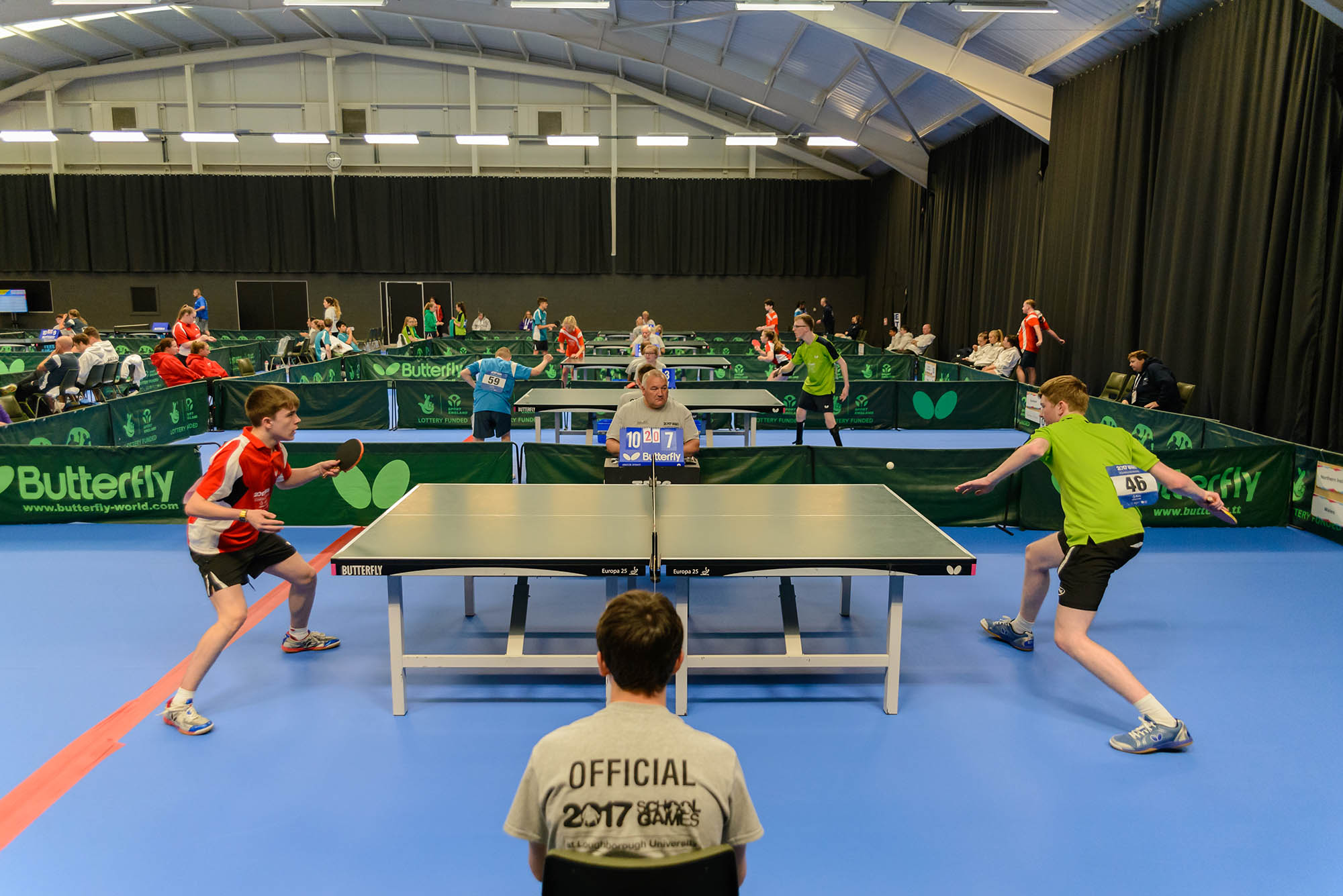 wide side view of table tennis matches taking place with two boys playing in foreground