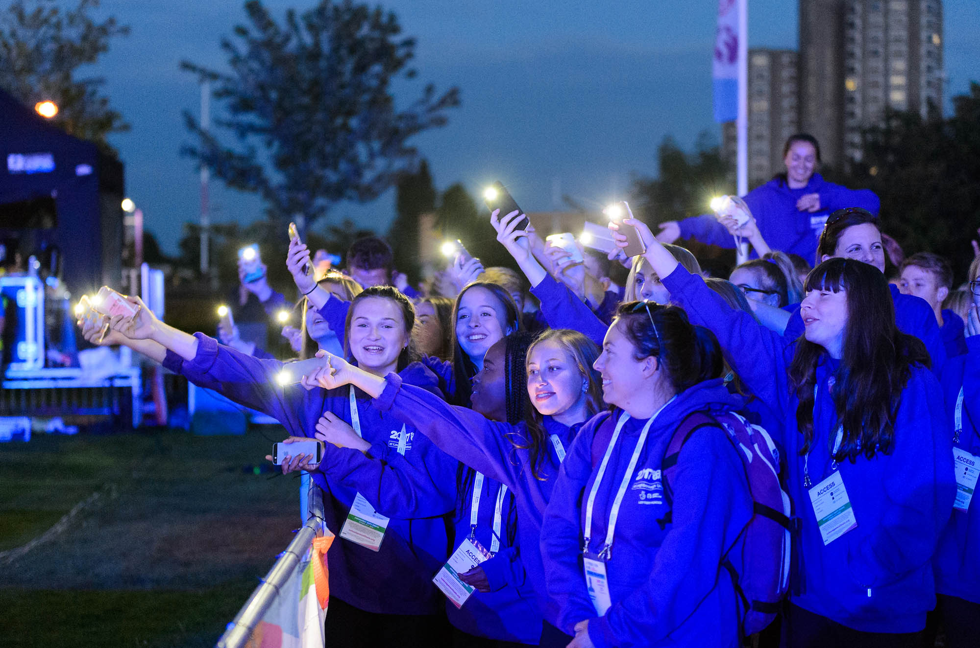 group of girls with lights on phone smiling at School Games opening ceremony