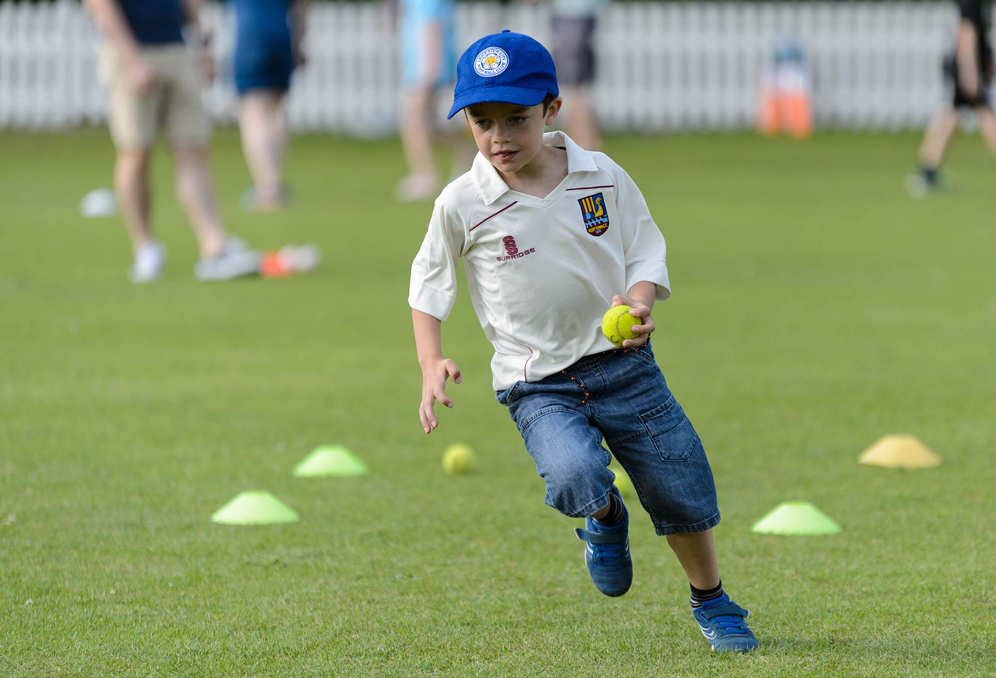 young boy wearing cap running with ball