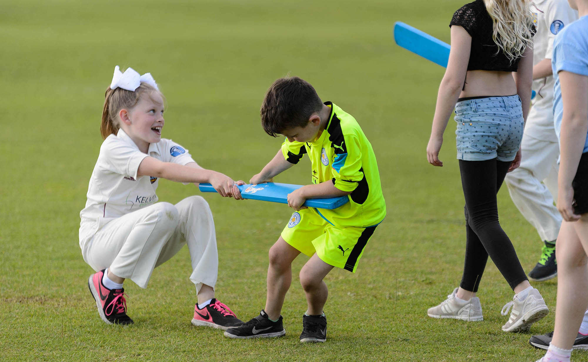 girl and boy playfully fighting over a cricket bat