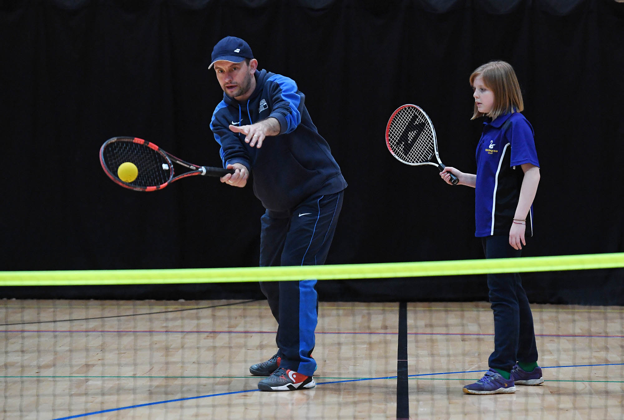 man coaching girl indoor tennis