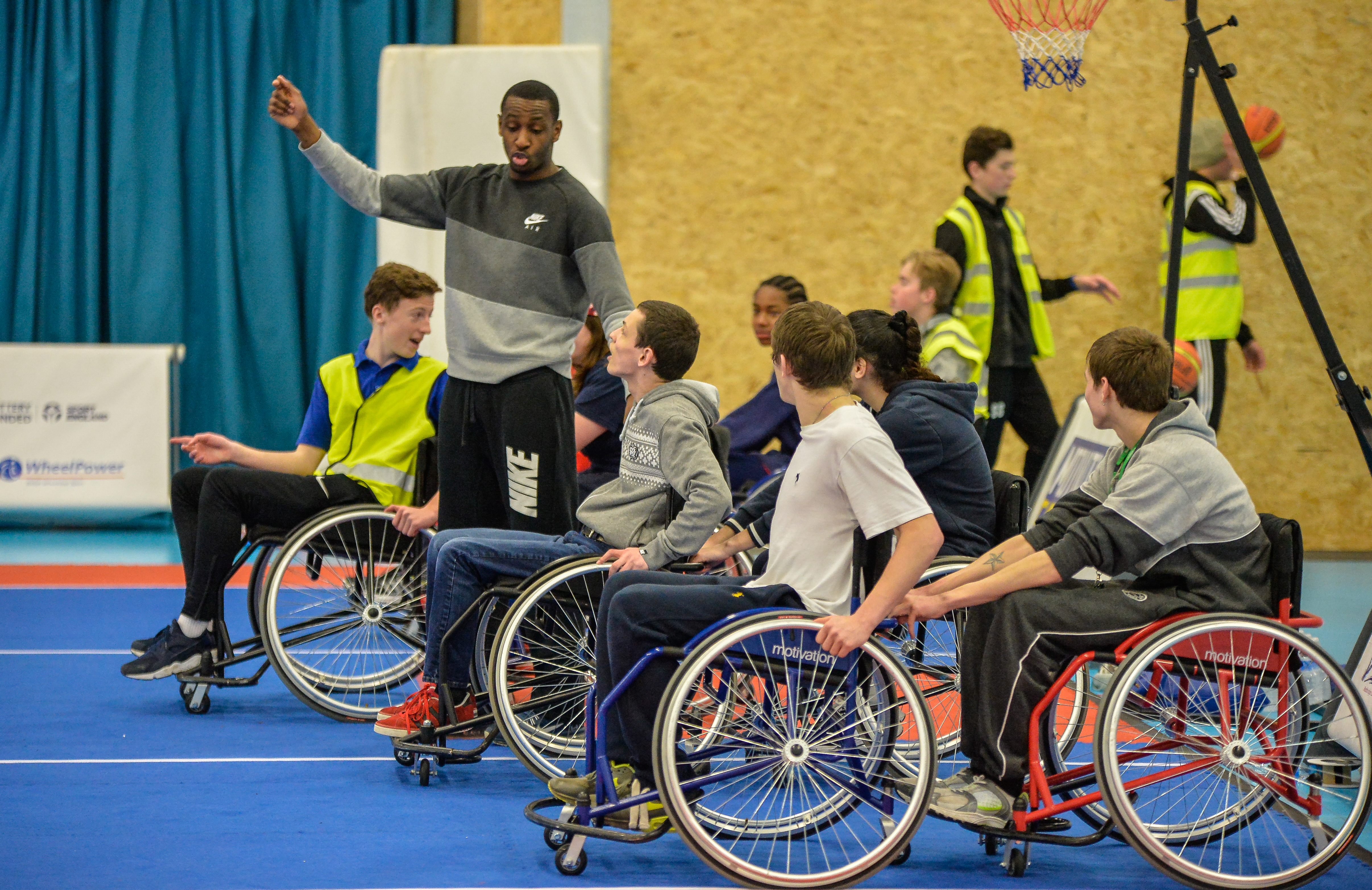 man coaching wheelchair basketball players