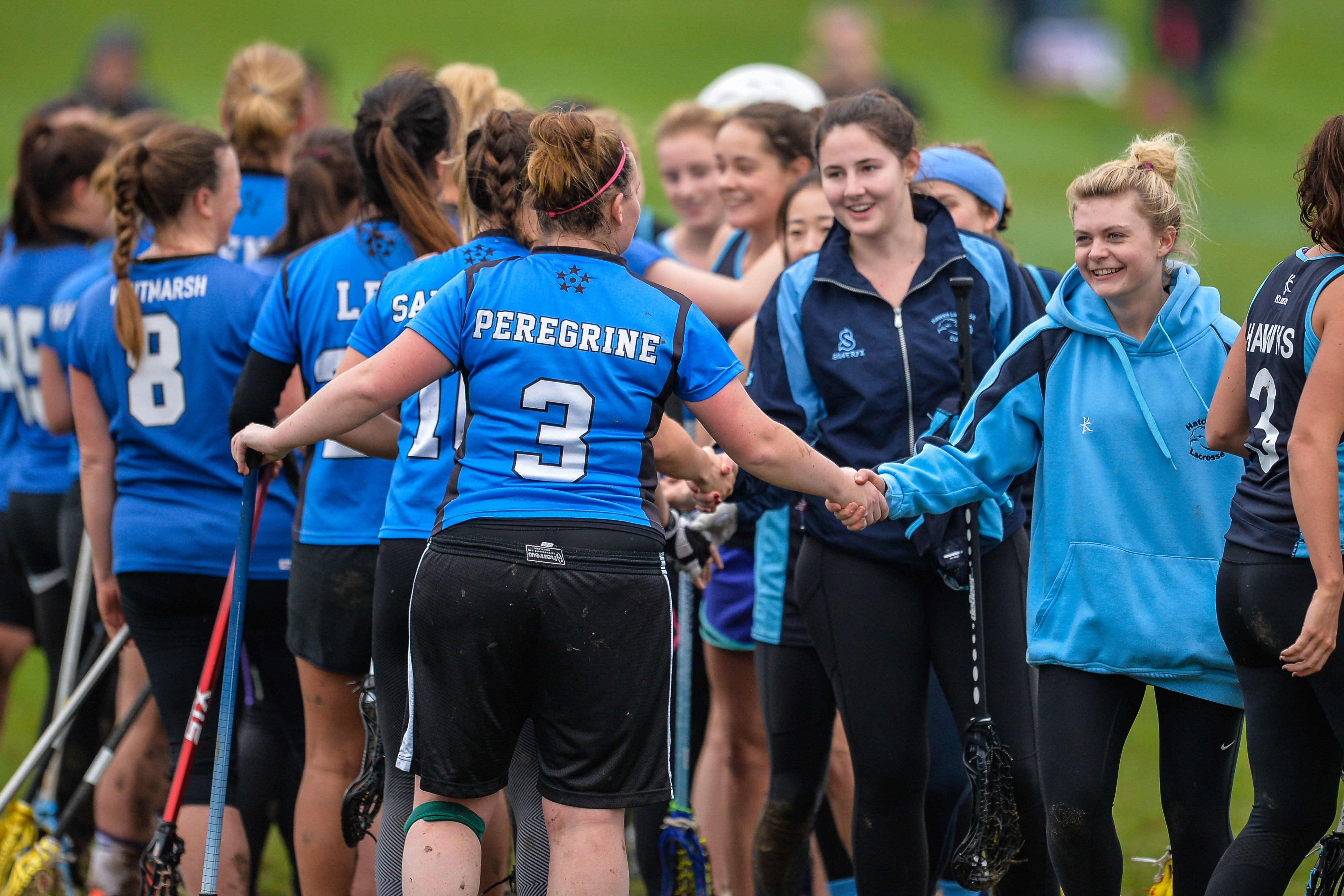 female lacrosse players shaking hands