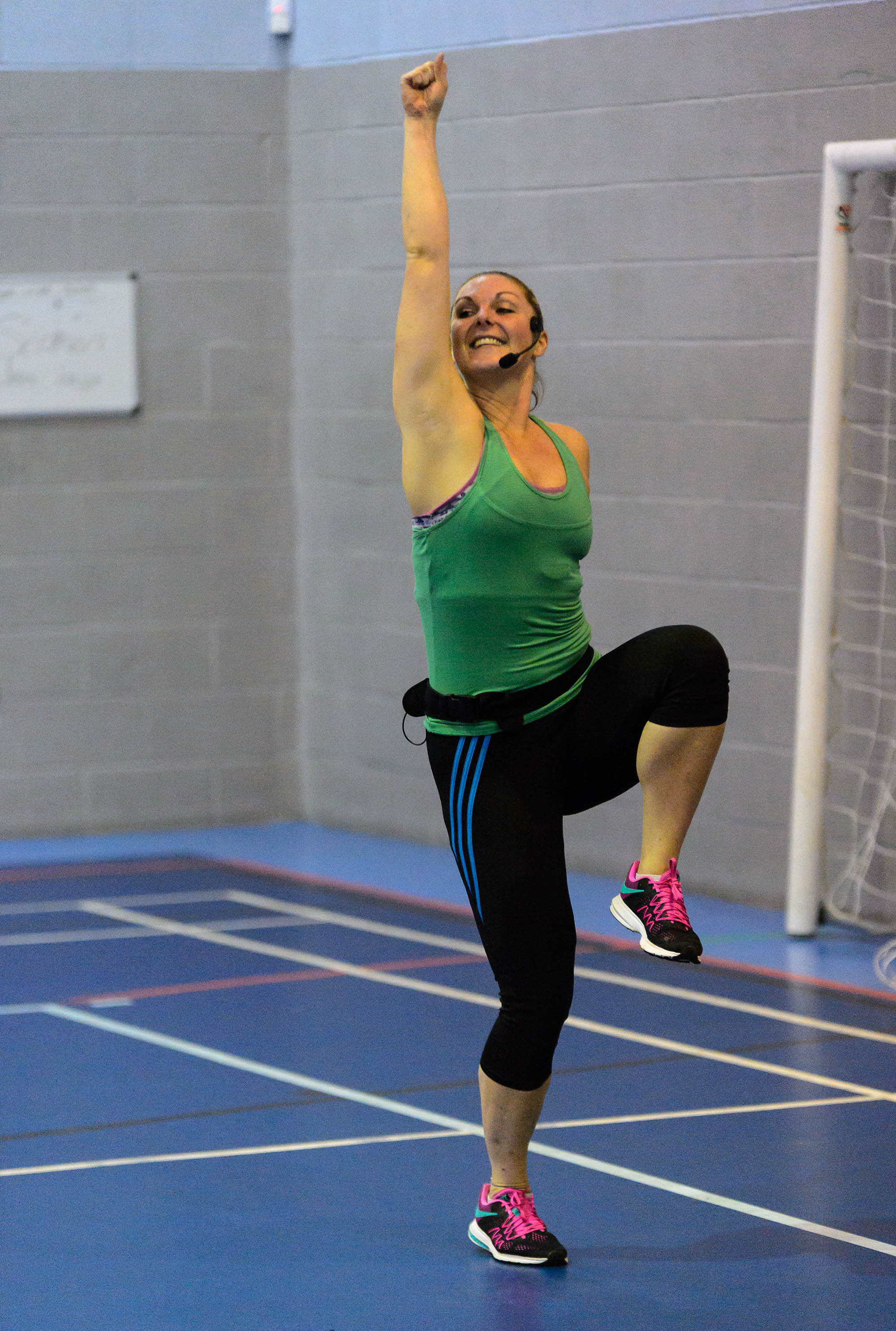 woman fitness instructor smiling mid-demonstration