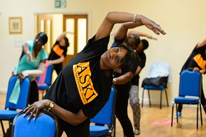 A group of women taking part in a chair exercise session.