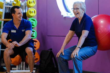 Elderly lady using exercise ball with coach