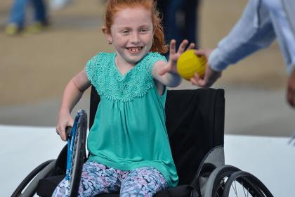 Young girl in wheelchair receiving ball