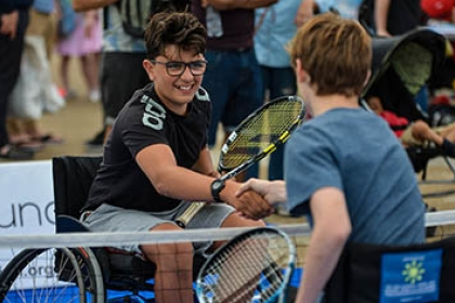 Two boys playing wheelchair tennis shake hands at the net
