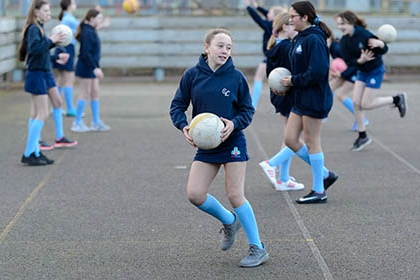 A group of college girls playing netball.