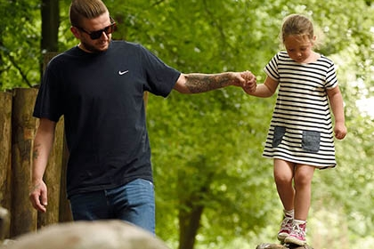 A father holding his daughter's hand as she walks along a tree trunk in a forest.