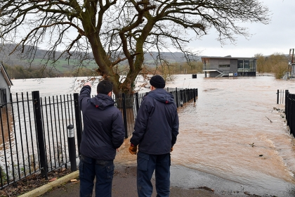 Two men survey the scene of a flooded sports pitch and pavilion