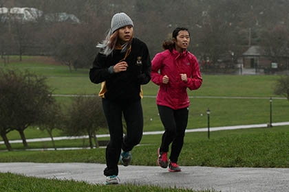 Two joggers run through a park