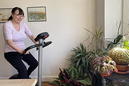 A woman rides an exercise bike in her own home.