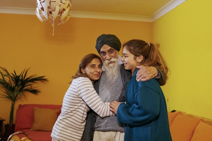 A family of three embracing in their living room.