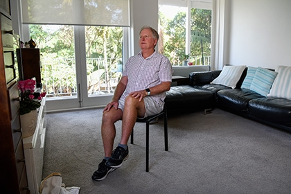 An older man performs seated exercises at home.