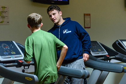 A Street Games volunteer instructs a boy how to run on a treadmill
