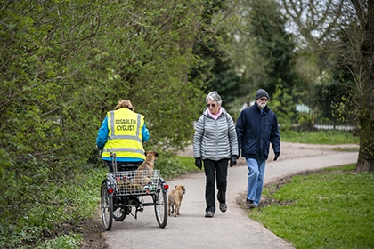 A disabled cyclist, riding a trike, rides with her down past an elderly couple on a path.