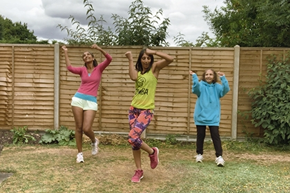 Three women perform Zumba exercises in a garden.