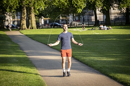A man skipping on a path in a park