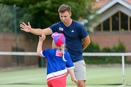 A tennis coach high-fives a girl during a coaching session.