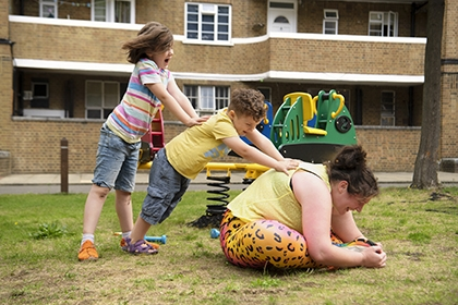 A woman sits on the floor, stretching, while her two children help her by pushing on her back.