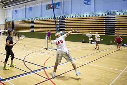 A group of people play badminton in a sports hall.