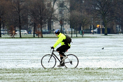 A man cycles in the snow