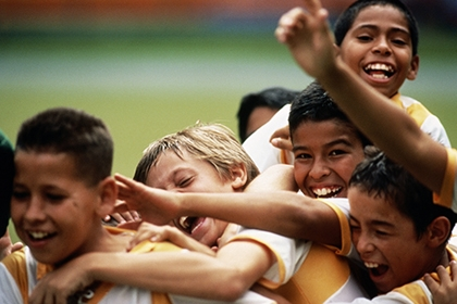 A group of young boys celebrate at a football match. Credit: Juan Silva/The Image Bank via Getty Images.