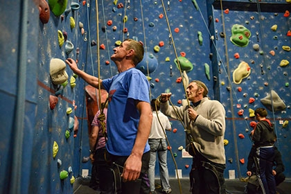 Leaders hold ropes at the foot of a climbing wall