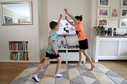 Two boys perform exercise in their living room as part of Joe Wicks' 'PE with Joe' programme.