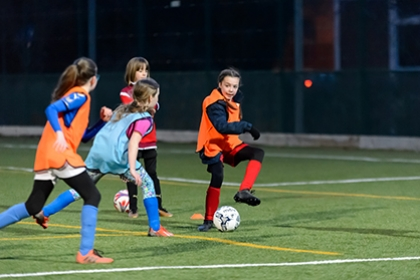 A group of girls play football on an artificial pitch.