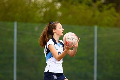 A girl plays netball outside