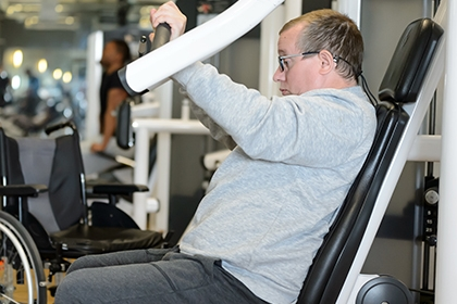 A man uses a chest press machine in the gym