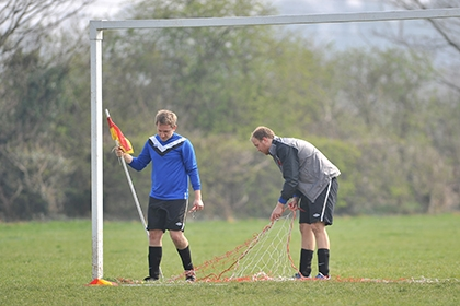 Players set up the nets and corner flags for a football match