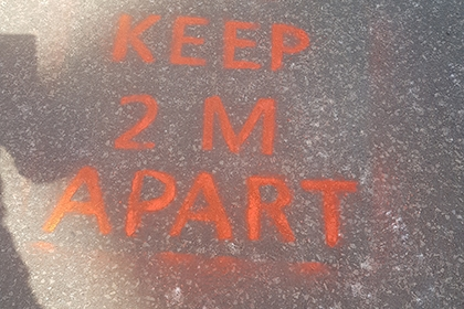 A social distancing message painted on the floor in a Rugby Borough Council park