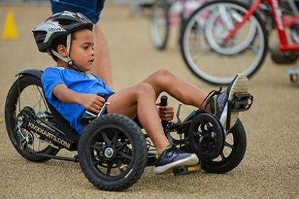 A boy rides an adapted recumbent tricycle