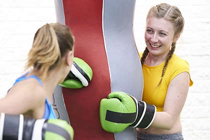 Two women work out on a heavy bag