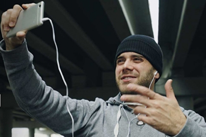 A man in a tracksuit top talks to his phone, while wearing headphones, delivering a sports session online.