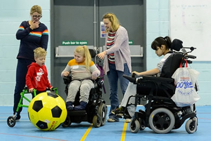 Two child wheelchair users and a and a boy with a walking frame play with a giant football