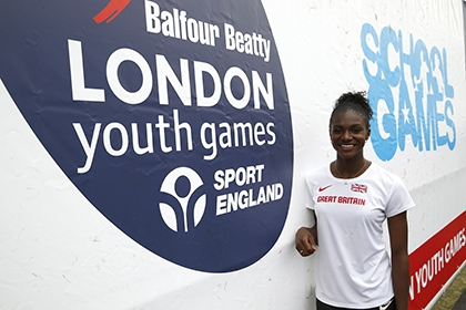 Dina Asher-Smith at the 2015 London Youth Games, standing in front of a sponsor banner
