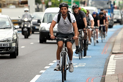 Cyclists ride on a cycle superhighway in London, alongside cars