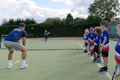 Children line up alongside a tennis court as a coach demonstrates a drill.