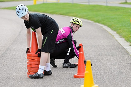 Two young cyclists lay out cones for a skills drill.