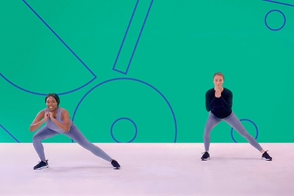 Two girls perform side lunges in an exercise class as part of a Studio You video