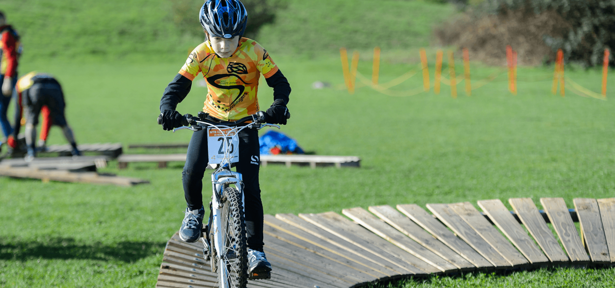 Boy riding bicycle outdoors on wooden path
