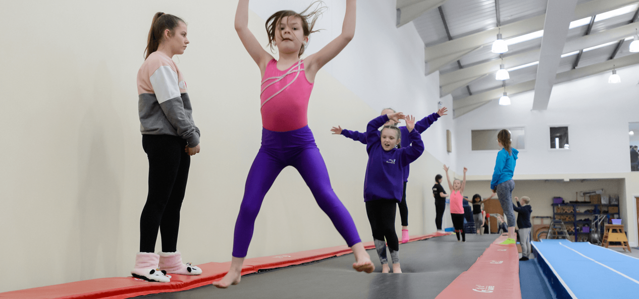 Children jumping on long trampoline with supervision