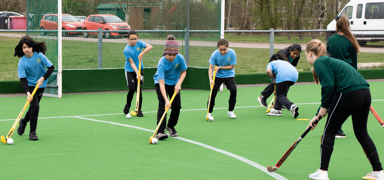 Children playing hockey on outdoor artificial pitch