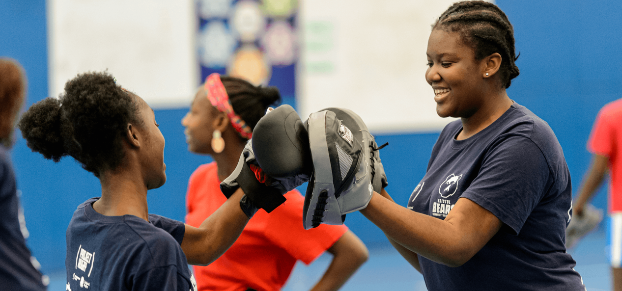 Boxing coach helping girl using pads